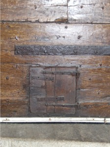 The dog door in the door of Mullion Church. This church previously had carved beams and rafters from oaks of the Goonhilly Forest, now long felled, but a portion is preserved and on display.