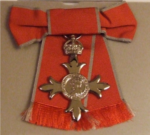 The medal is cruciform, surmounted by a crown. The inscription reads FOR GOD AND THE EMPIRE. The ribbon is rose pink with pearl grey edges.